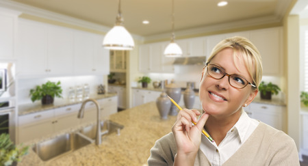 staging: Attractive Daydreaming Woman with Pencil Inside Beautiful Custom Kitchen. Stock Photo