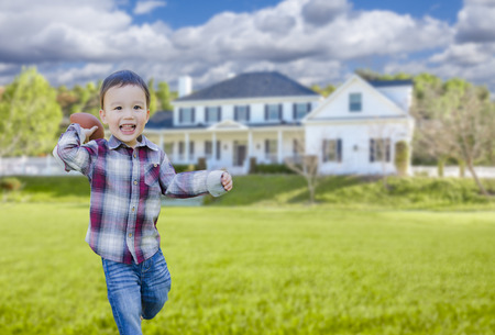 front of: Cute Happy Mixed Race Boy Playing Ball in His Front Yard. Stock Photo