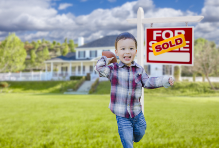 Cute Mixed Race Boy Playing Ball in Front Yard Near Sold Real Estate Sign. Stock Photo