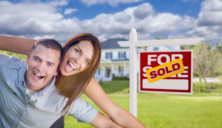 Playful Excited Military Couple In Front of Home with Sold Real Estate Sign. Banque d'images