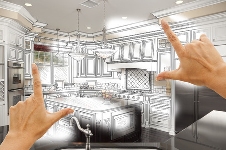 home renovation: Female Hands Framing Custom Kitchen Design Drawing and Photo Combination. Stock Photo