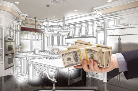 hundreds: Hand Holding Stacks of Money Over Custom Kitchen Design Drawing and Photo Combination.