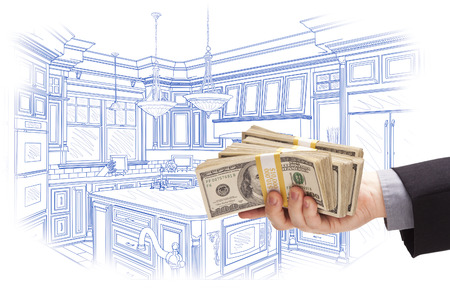 hundreds: Hand Holding Stacks of Money Over Custom Kitchen Design Drawing. Stock Photo