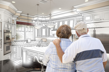 looking over: Senior Couple Looking Over Custom Kitchen Design Drawing and Photo Combination.