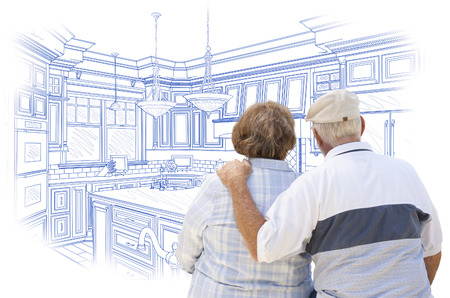 the elderly residence: Curious Senior Couple Looking Over Blue Custom Kitchen Design Drawing. Stock Photo
