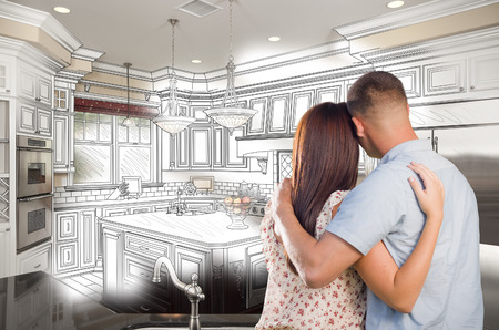 home construction: Young Military Couple Looking Inside Custom Kitchen and Design Drawing Combination.