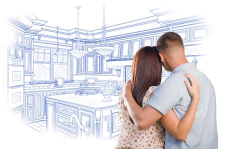 kitchen remodelling: Curious Young Military Couple Looking Over Custom Kitchen Design Drawing. Stock Photo