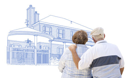 home shopping: Curious Embracing Senior Couple Looking At House Drawing on White. Stock Photo