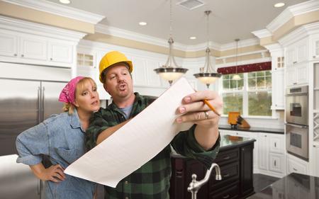 Männlich Auftragnehmer in Bauarbeiterhelm diskutieren Pläne mit Frau im Kunden Kitchen Interior.