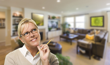 custom home: Attractive Daydreaming Woman with Pencil Inside Beautiful Living Room. Stock Photo