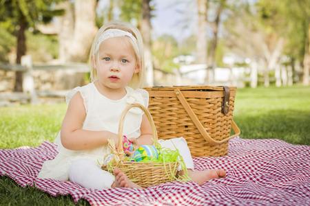 picnic blanket: Ni�a linda que disfruta de su Goza Huevos de Pascua en Manta de picnic en la hierba.