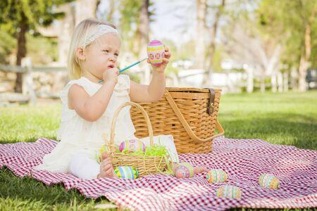 picnic blanket: Beb� lindo que le gusta colorear sus huevos de Pascua en Manta de picnic en la hierba. Foto de archivo