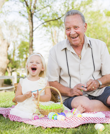 Loving Grandfather and Granddaughter Coloring Easter Eggs Together on Picnic Blanket At The Park. photo