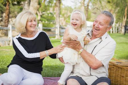 愛情のこもった孫娘と祖父母外側公園で遊ぶ。