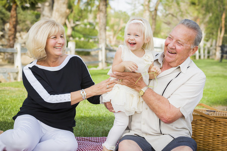 Affectionate Granddaughter and Grandparents Playing Outside At The Park. 版權商用圖片 - 37093178