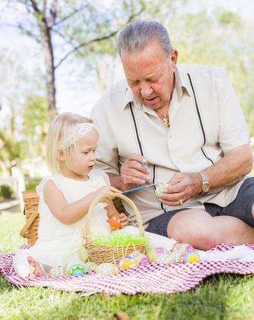 picnic blanket: Abuelo y nieta cari�osos para colorear los huevos de Pascua Juntos en Manta de picnic en el parque.