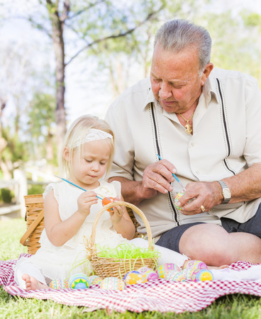 egg hunt: Loving Grandfather and Granddaughter Coloring Easter Eggs Together on Picnic Blanket At The Park.