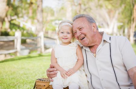 abuelo: Abuelo y nieta cari�osos que abrazan afuera en el parque.