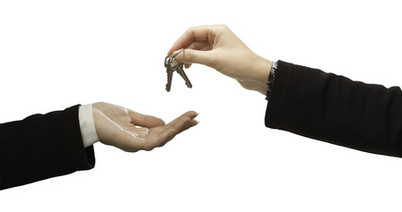 Woman Handing Over Woman Set Of New Keys Isolated on White. Archivio Fotografico