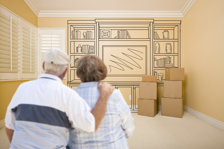 real estate planning: Hugging Senior Couple In Empty Room with Shelf Design Drawing on Wall.
