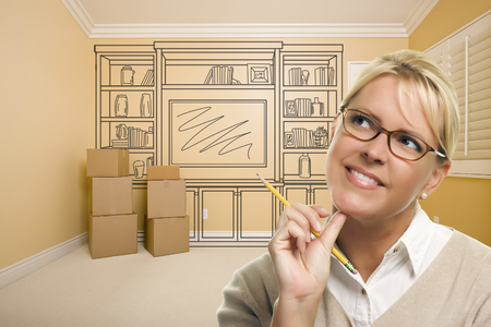 built in: Daydreaming Woman Holding Pencil In Empty Rom with Built In Shelf Design Drawing on Wall.