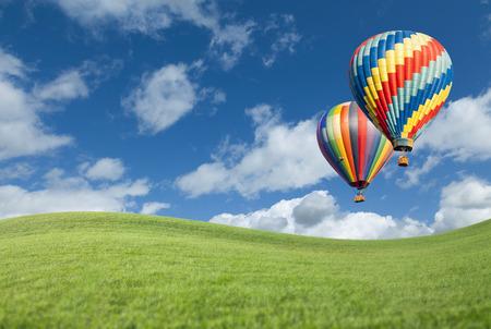Twee Hot Air Balloons Up In de mooie blauwe hemel met gras veld onder.