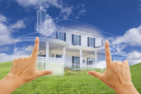construction plans: Female Hands Framing Beautiful Custom House Drawing and Ghosted House Above Grass Field. Stock Photo