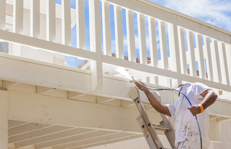 house painter: House Painter Wearing Facial Protection Spray Painting A Deck of A Home.