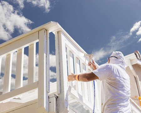 painter: House Painter Wearing Facial Protection Spray Painting A Deck of A Home.