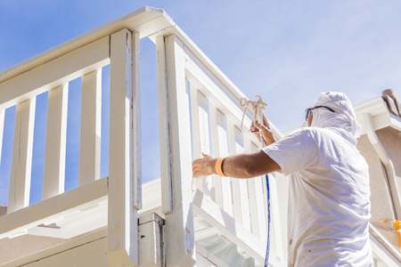 painting: House Painter Wearing Facial Protection Spray Painting A Deck of A Home.