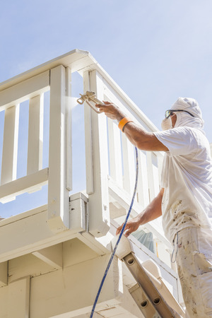 man painting: House Painter Wearing Facial Protection Spray Painting A Deck of A Home.