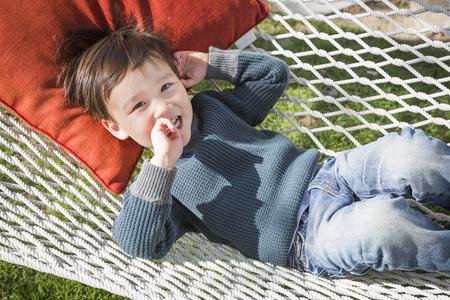 mixed race boy: Cute Mixed Race Boy Relaxing in His Hammock.