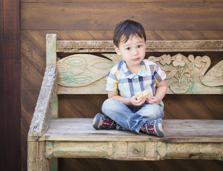 mixed race boy: Cute Relaxed Mixed Race Boy Sitting on Bench Eating His Sandwich.