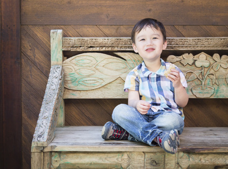 Cute Relaxed Mixed Race Boy Sitting on Bench Eating His Sandwich.