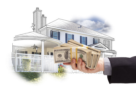 handing: Hand Holding Thousands of Dollars In Cash Over House Drawing and Photo Area. Stock Photo
