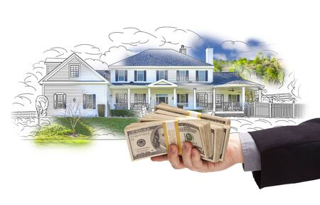 Hand Holding Thousands of Dollars In Cash Over House Drawing and Photo Area. Stock Photo