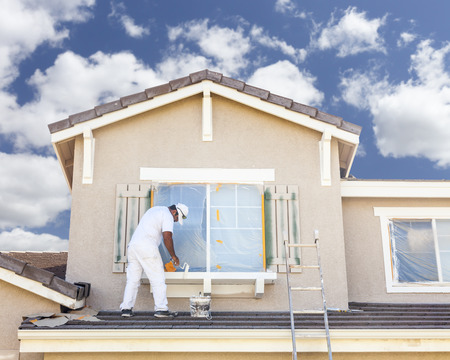 building material: Busy House Painter Painting the Trim And Shutters of A Home.