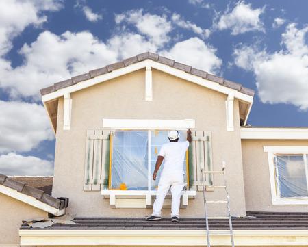 Drukke Huis Schilder die de trim en Luiken van een huis. Stockfoto