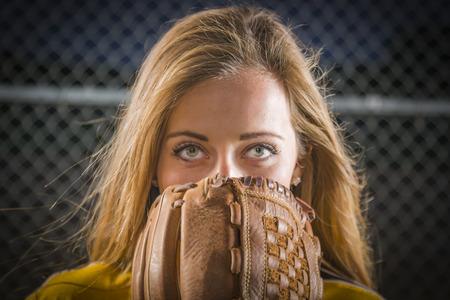 softbol: Dramático Mujer joven con el Guante de Softbol tapándose la cara al aire libre. Foto de archivo