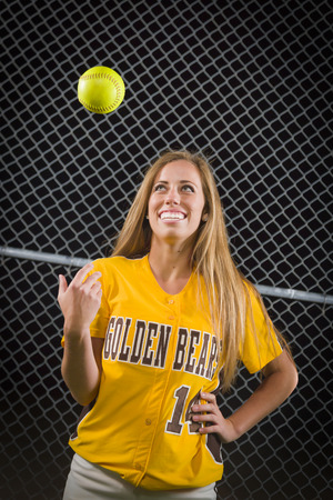 softball player: Young Female Softball Player Portrait with Ball in the Air.