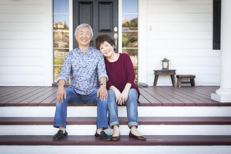 tercera edad: Atractivo feliz pareja china mayor que se sienta en las escaleras de su casa.