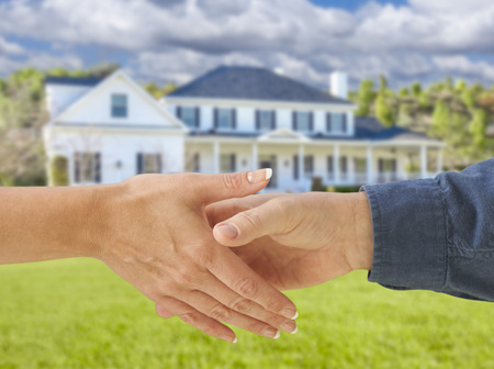 Man and Woman Shaking Hands in Front of a Beautiful New House. Stockfoto