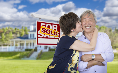 new ages: Attractive Affectionate Senior Chinese Couple In Front of Beautiful House and Sold For Sale Real Estate Sign.