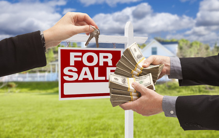 short sale: Man Handing Woman Thousands of Dollars For Keys in Front of House and For Sale Real Estate Sign.