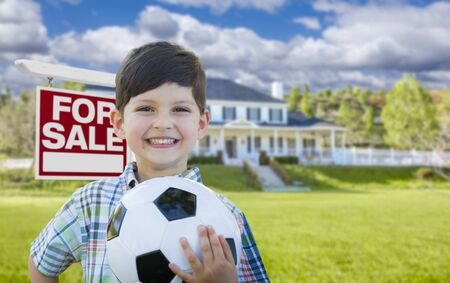 front house: Playful Young Boy Holding Soccer Ball In Front of House and For Sale Real Estate Sign.