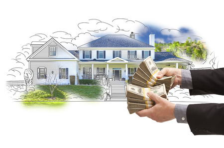 thousands: Hand Holding Thousands of Dollars In Cash Over House Drawing and Photo Area. Stock Photo
