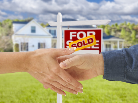 front of: Man and Woman Shaking Hands in Front of a Beautiful New House and Sold For Sale Real Estate Sign. Stock Photo