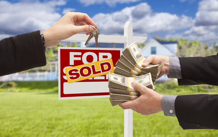 short sale: Man Handing Woman Thousands of Dollars For Keys in Front of House and Sold For Sale Real Estate Sign.