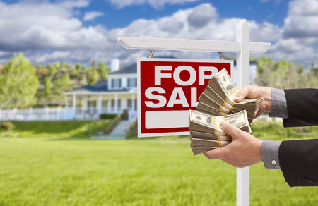 short sale: Man Handing Over Thousands of Dollars in Front of House and For Sale Real Estate Sign. Stock Photo