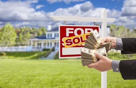 Mann Auslieferung über Tausende von Dollar in Front of House und Verkauft Verkauf Immobilien-Zeichen. Lizenzfreie Bilder